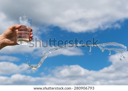 Splashing glass of  water against summer sky. - stock photo