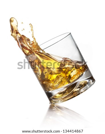 Splashing of whiskey out of glass isolated on white - stock photo