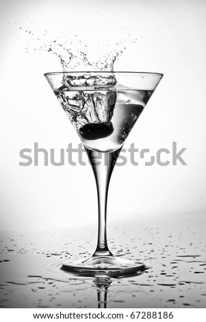 Splashing olive into a martini glass (black and white) - stock photo