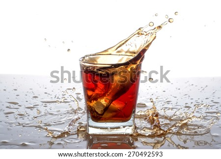 splashing out of the glass from falling ice cubes - stock photo