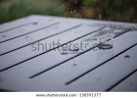 Splashing rain water droplets on wooden garden table close up - stock photo