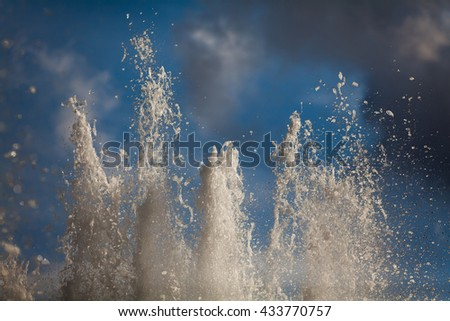 Splashing streams of fountains on background of a sky - stock photo