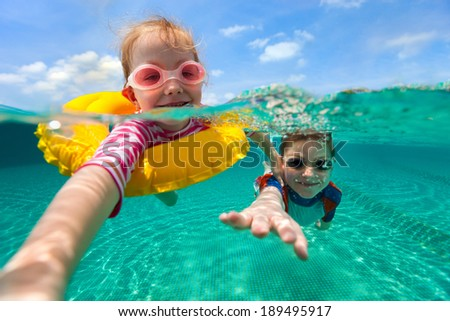 Split above and underwater photo of adorable kids having fun swimming on summer vacation - stock photo