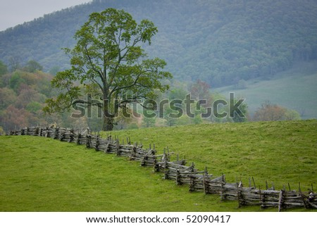 Split rail fence bisects hilltop pasture in Virginia. - stock photo