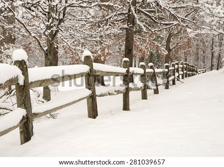 Split-rail fence with fresh snow and snow covered trees - stock photo