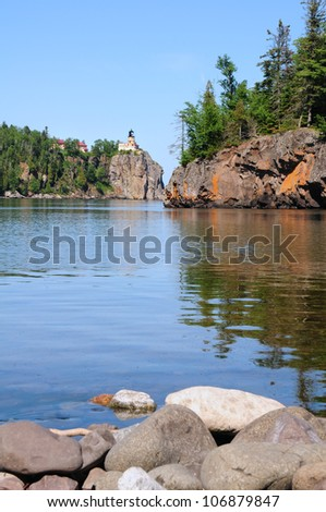 Split Rock Lighthouse on Cliff, rocks in foreground - stock photo