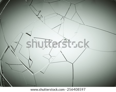 Splitted or cracked glass on grey vignetted background - stock photo