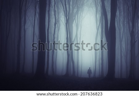 spooky dark forest with mysterious man walking on a path halloween theme - stock photo