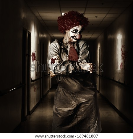Spooky dark horror portrait of a female doctor clown posing in a shady hospital corridor. Theatre nightmare - stock photo