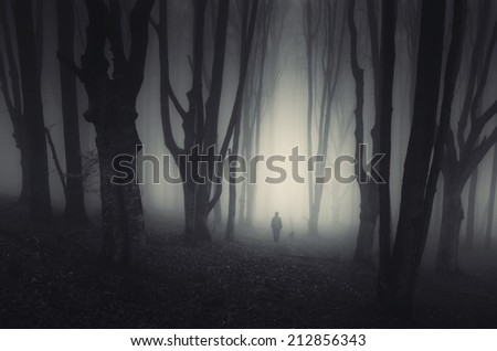 spooky forest landscape with man and twisted trees on halloween - stock photo