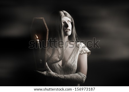 Spooky gothic girl walking through a haunted horror house with candle coffin during a chilling ghost tale - stock photo