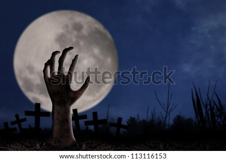 Spooky graveyard with zombie hand coming out of the ground - stock photo