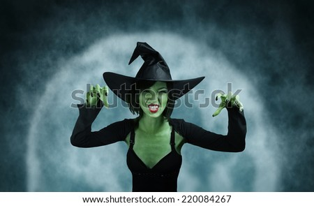 Spooky green witch performs magic on full moon background. Halloween, horror theme - stock photo