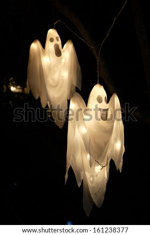 Spooky Halloween ghost against black background - stock photo