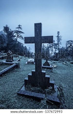 Spooky Halloween graveyard in fog in moonlight - stock photo