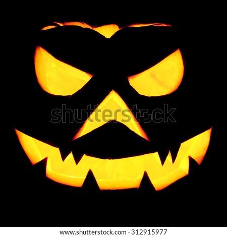 Spooky halloween pumpkin Jack O Lantern shiny inside on black  - stock photo