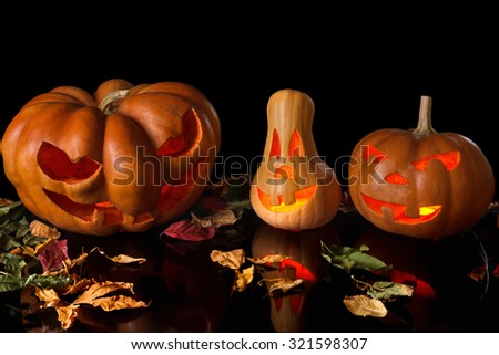 Spooky Halloween pumpkin with fallen leaves, a terrible fire and reflections. Isolated on black background - stock photo