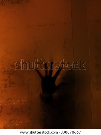 Spooky hand behind a glass in an abandoned house - stock photo