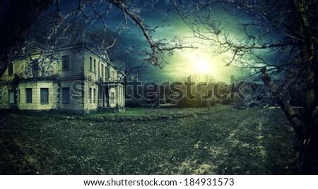 Spooky haunted house at dusk - stock photo