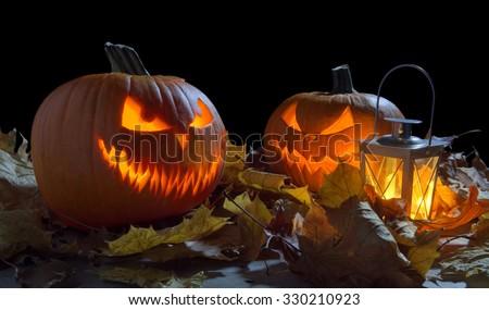 Spooky jack o lantern among dried leaves on black background - stock photo