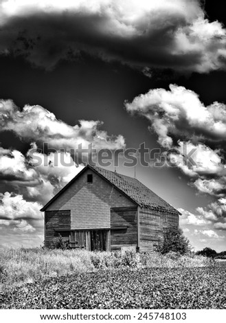 Spooky old desolate haunted barn with storm clouds overhead like you would see on Halloween in Black and White - stock photo