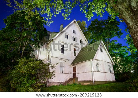 Spooky old haunted house at night in Finland. Trees surrounding the house frames it nicely. - stock photo