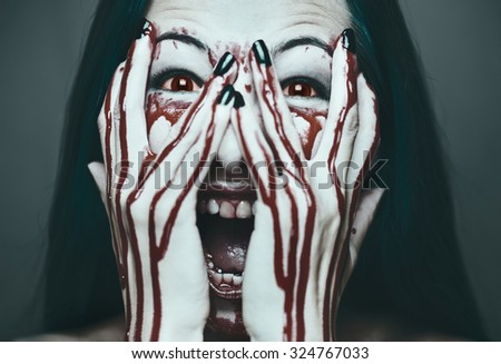 Spooky young woman screaming, her face and hands in blood. Halloween and horror theme. Monochrome image - stock photo