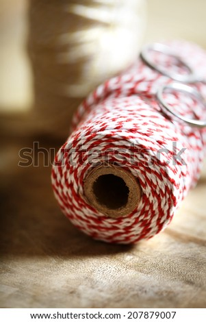 Spool of red and white twine with scissors on wooden background - stock photo