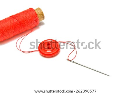 spool of red thread, button and needle on white  - stock photo