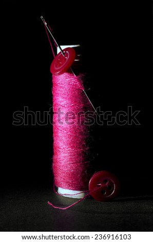 Spool of Red Thread with Needle and Red Buttons Isolated on Black Background - stock photo