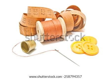 spool of thread, meter and yellow buttons on white - stock photo