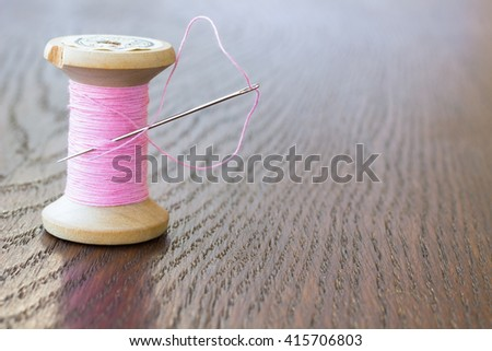 Spool of thread, needle and pink thread closeup - stock photo