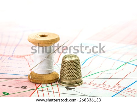 Spool of white sewing thread and thimble on pattern cutting - stock photo