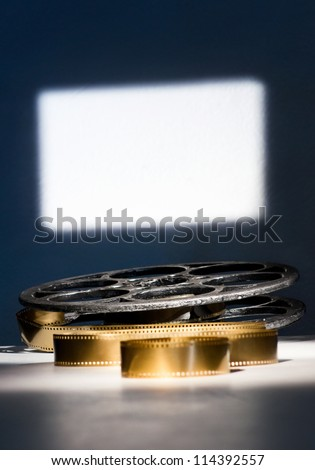Spool with golden film on the screen background - stock photo