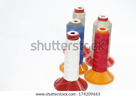 Spools of an industrial sewing machine in a factory - stock photo