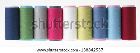 Spools of thread colored geometric composition on a white background - stock photo