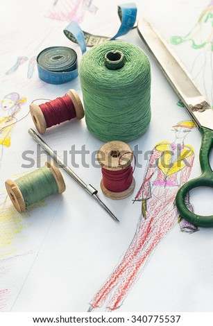 Spools of thread for sewing on the background of the sketch clothing - stock photo