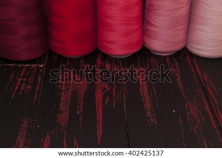 Spools of thread in the red range of sewing and needlework on the background of the old wooden table - stock photo