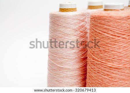 Spools of thread peach color on a white background - stock photo