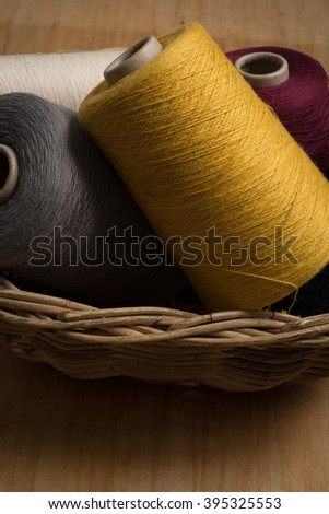 Spools of yellow, red, grey, and white thread in wicker basket. - stock photo