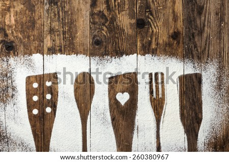 Spoon and fork, flour sprinkled around the wooden plank. - stock photo