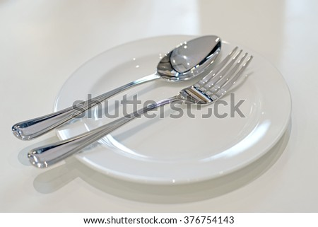 spoon and fork on empty white plate - stock photo