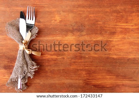 Spoon and fork on wooden table - stock photo