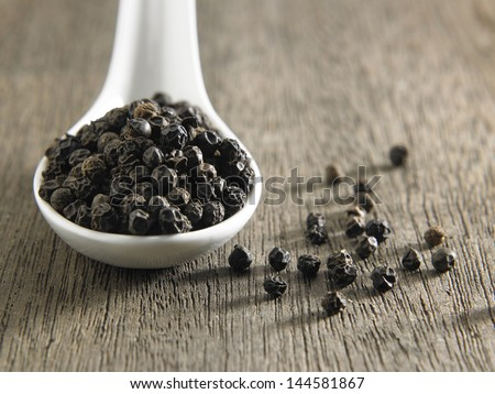 spoon full of  black peppercorn - stock photo