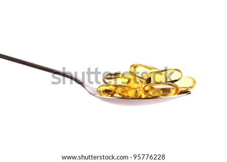 spoon full of fish oil capsules - stock photo