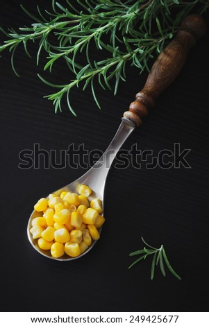 spoon full of pickled corn and rosemary on a black wooden background. home preservation.health and diet food - stock photo
