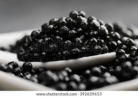 spoon of black caviar close-up in a white bowl side view horizontal - stock photo
