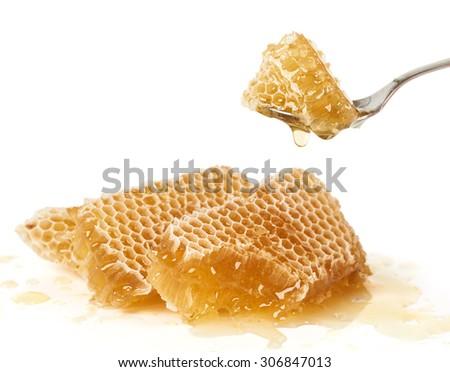 Spoon of raw honey over pieces of honey comb                                - stock photo