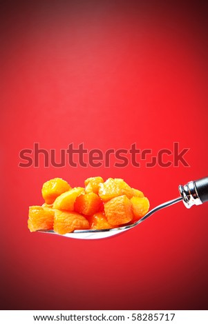 spoon with apricot pieces on a red background - stock photo