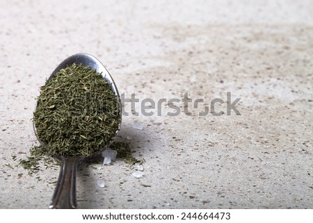 Spoon with dried herb and salt on the stone background. - stock photo